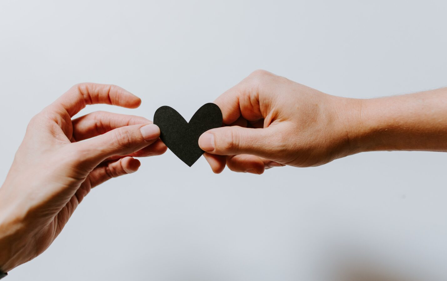 An image showing two hands holding a black heart. This is a way to achieving great customer experience