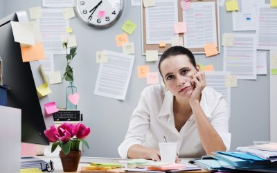 Tired frustrated female office worker at desk looking at camera.