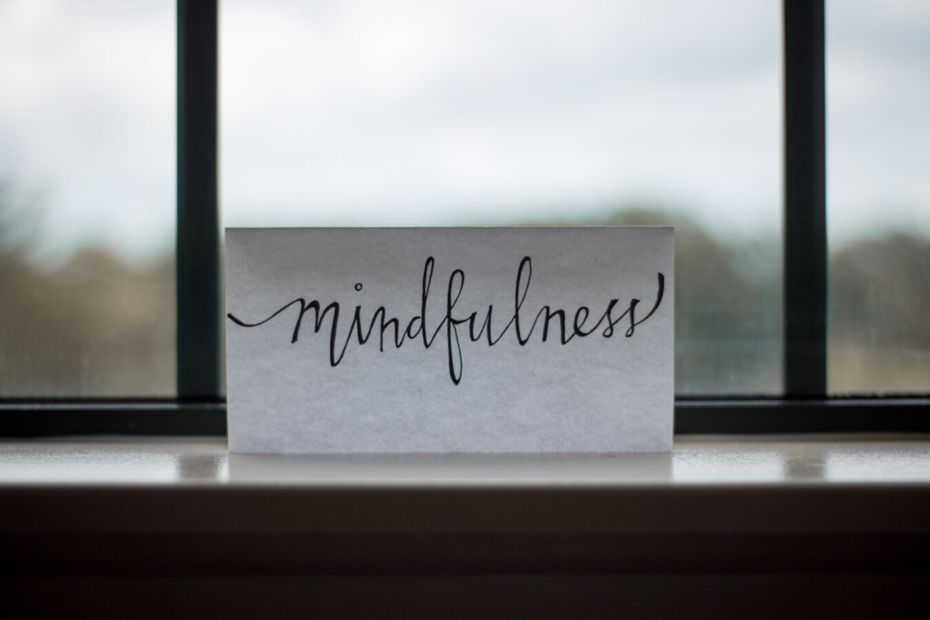 The word mindfulness is written on a piece of paper, representing one of the key things in building CSR strategies.
