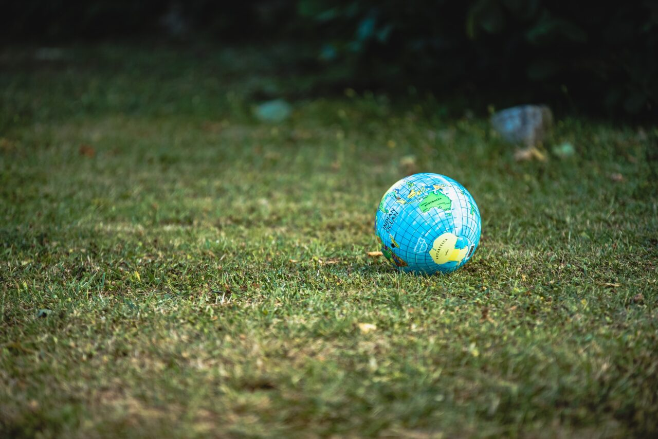 A world toy on the grass represents the importance of having sustainability development goals.