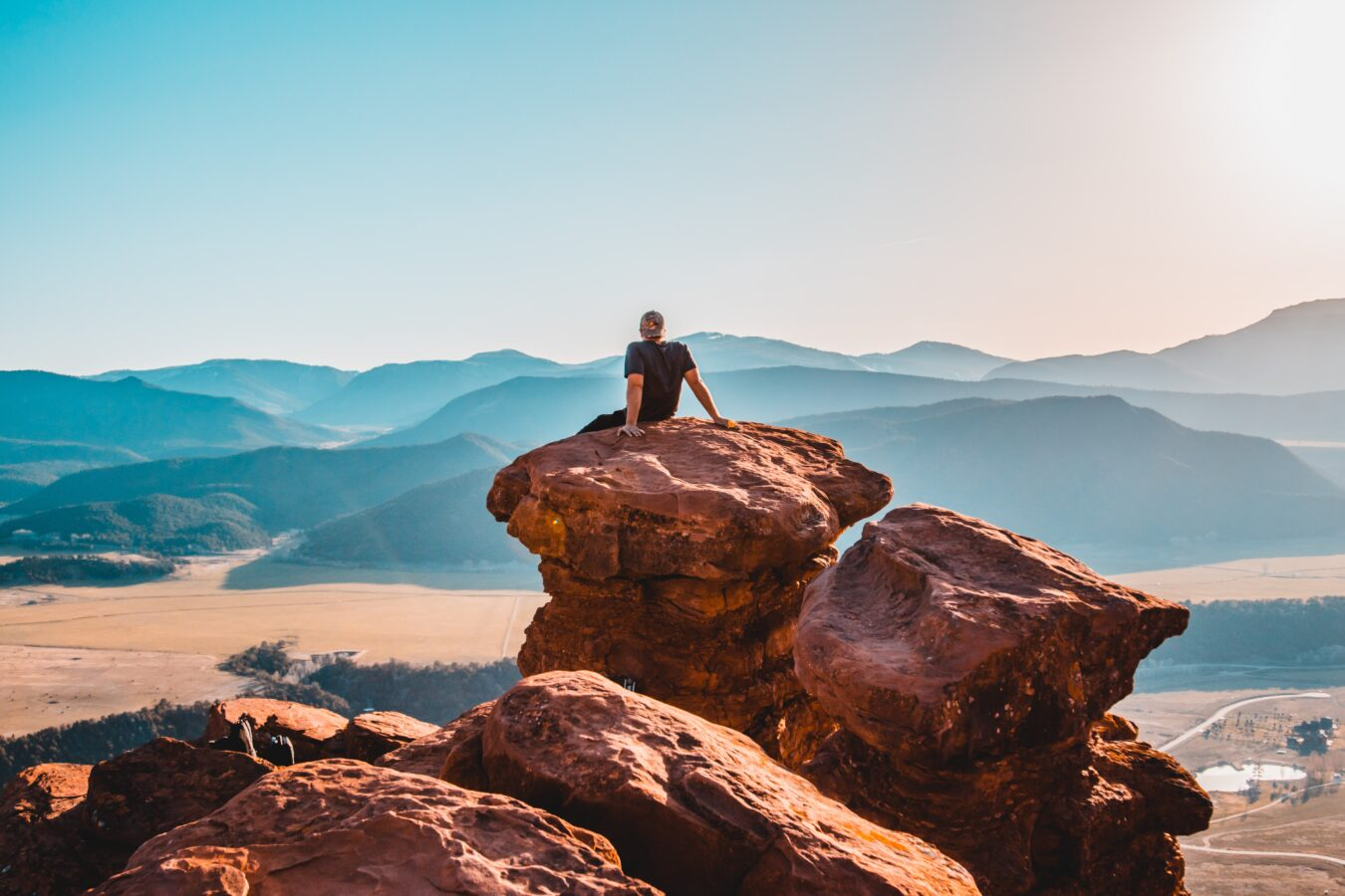 A person sits on the rocks thinking about improving CX with the help of hiking tips.