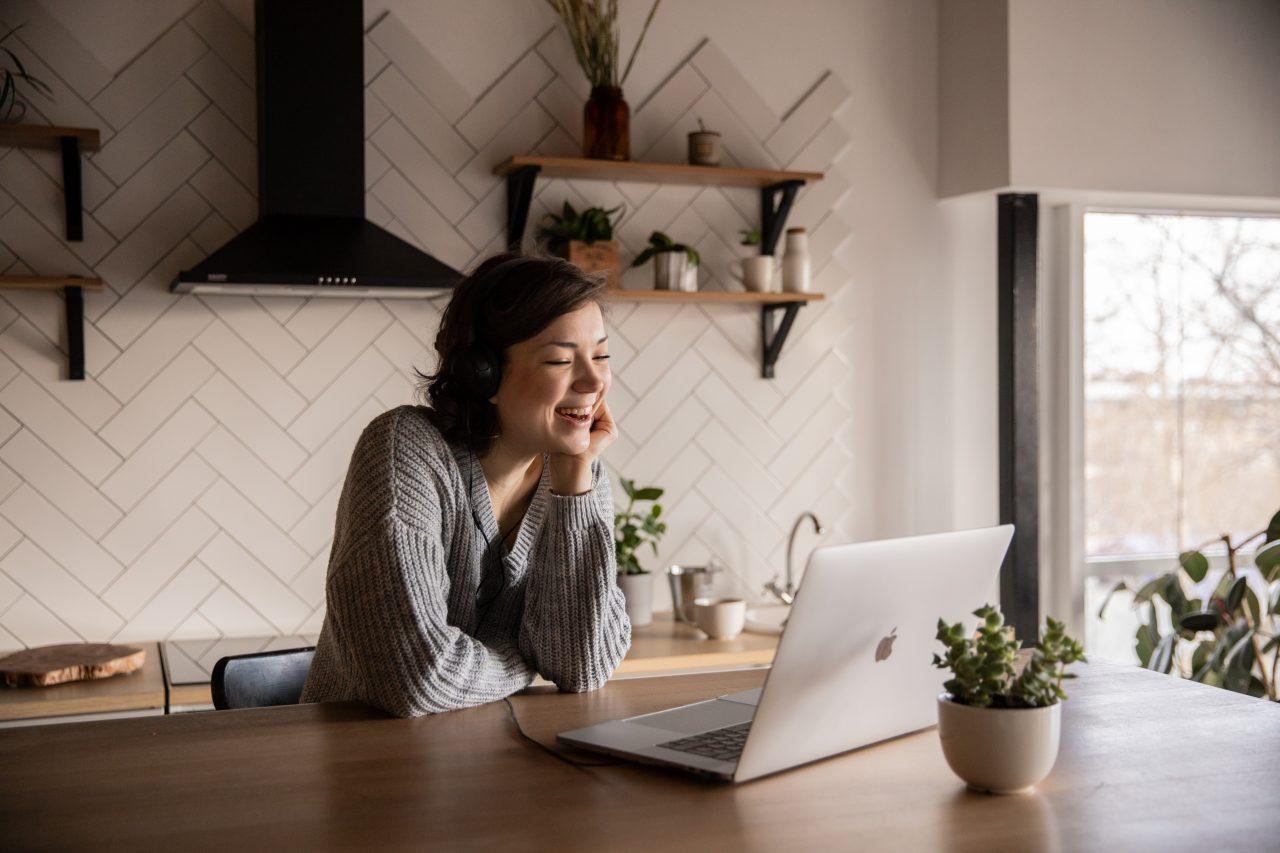 smiling-woman-talking-via-laptop-in-kitchen-4049992-1280x853.jpg
