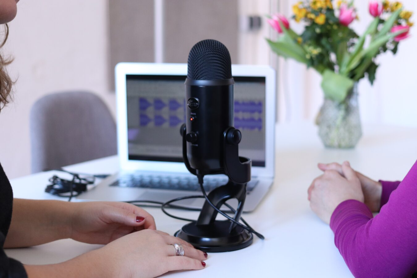 a microphone and a flower on the table showing an interview about the importance of applying emotional intelligence in CX