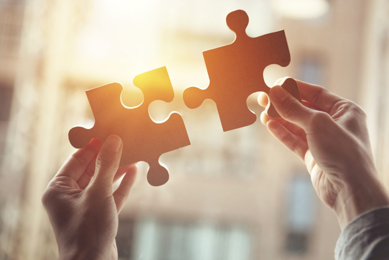 an image showing two hands connecting a puzzle. This is a symbol for CX strategy.
