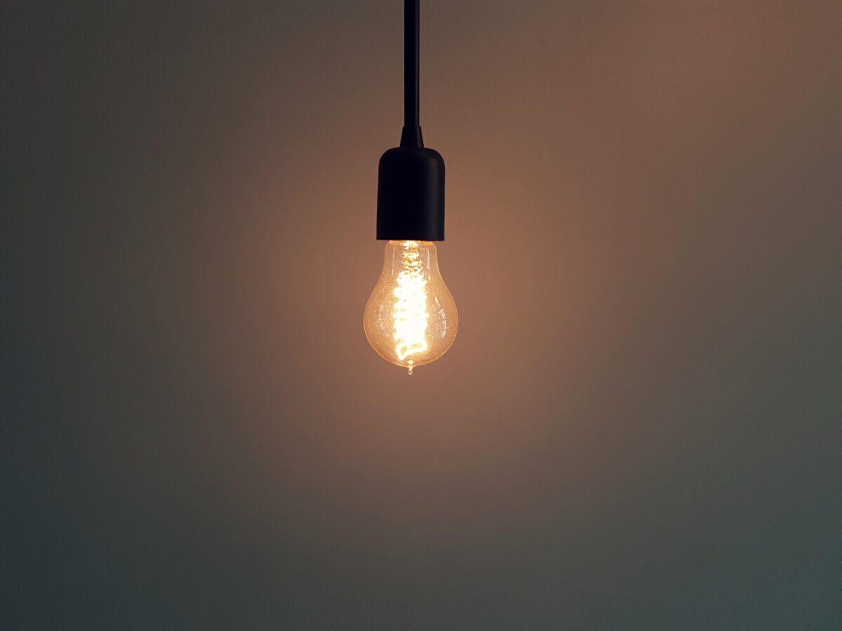 A lightbulb glowing in the dark represents innovation in turbulent times.