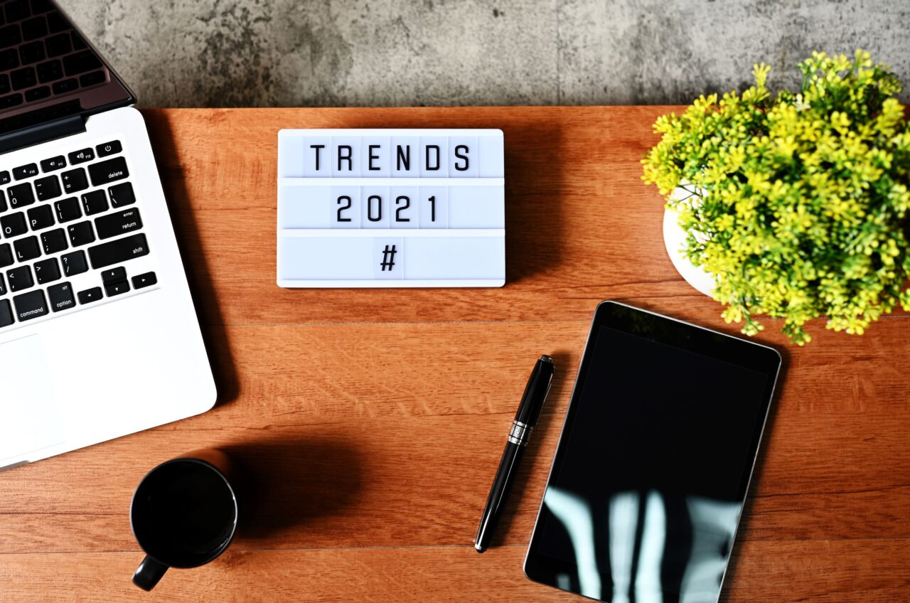 A board on the desk contains the words Customer Experience Trends in 2021.