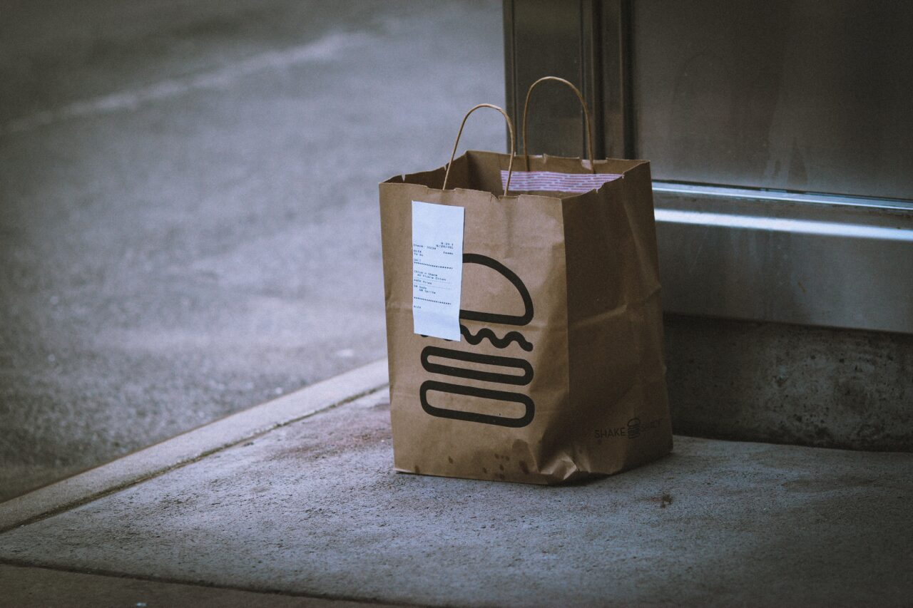 A bag with the hamburger illustration stands alone on the sidewalk and shows customer engagement is key to success because disengaged people are not inclined to buy stuff.