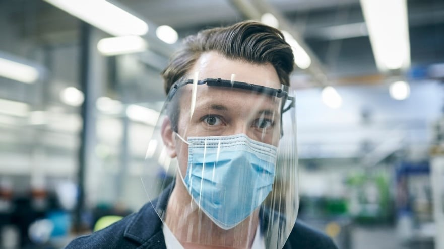 A man with a mask shows how people work during the COVID-19 pandemic.