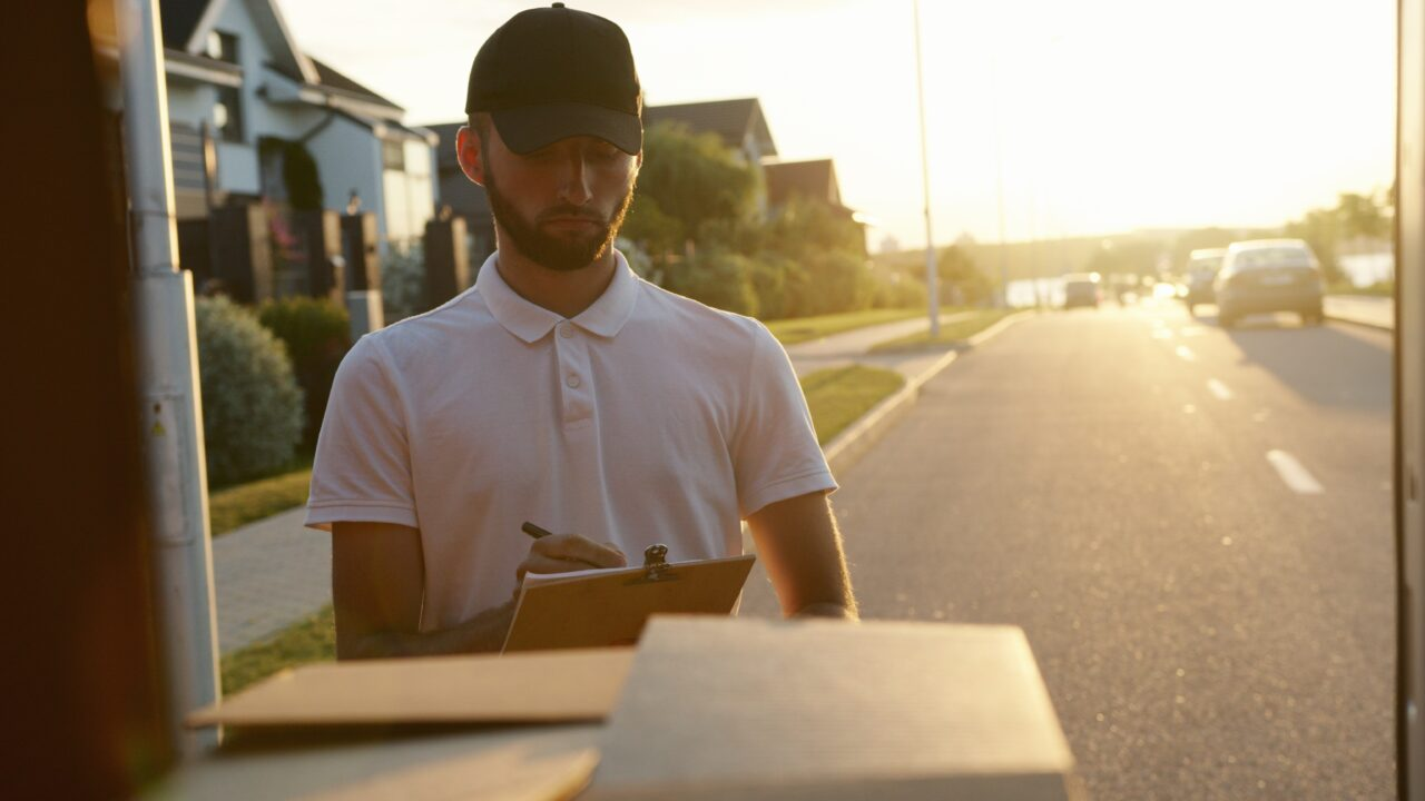 A courier delivers a package as the last step in the last-mile delivery.