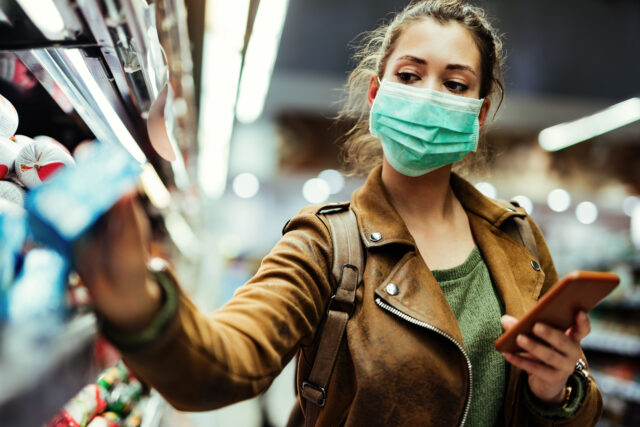 A young woman with a face mask is buying a product in a store. It demonstrate a customer experience of buying during the covid-19.