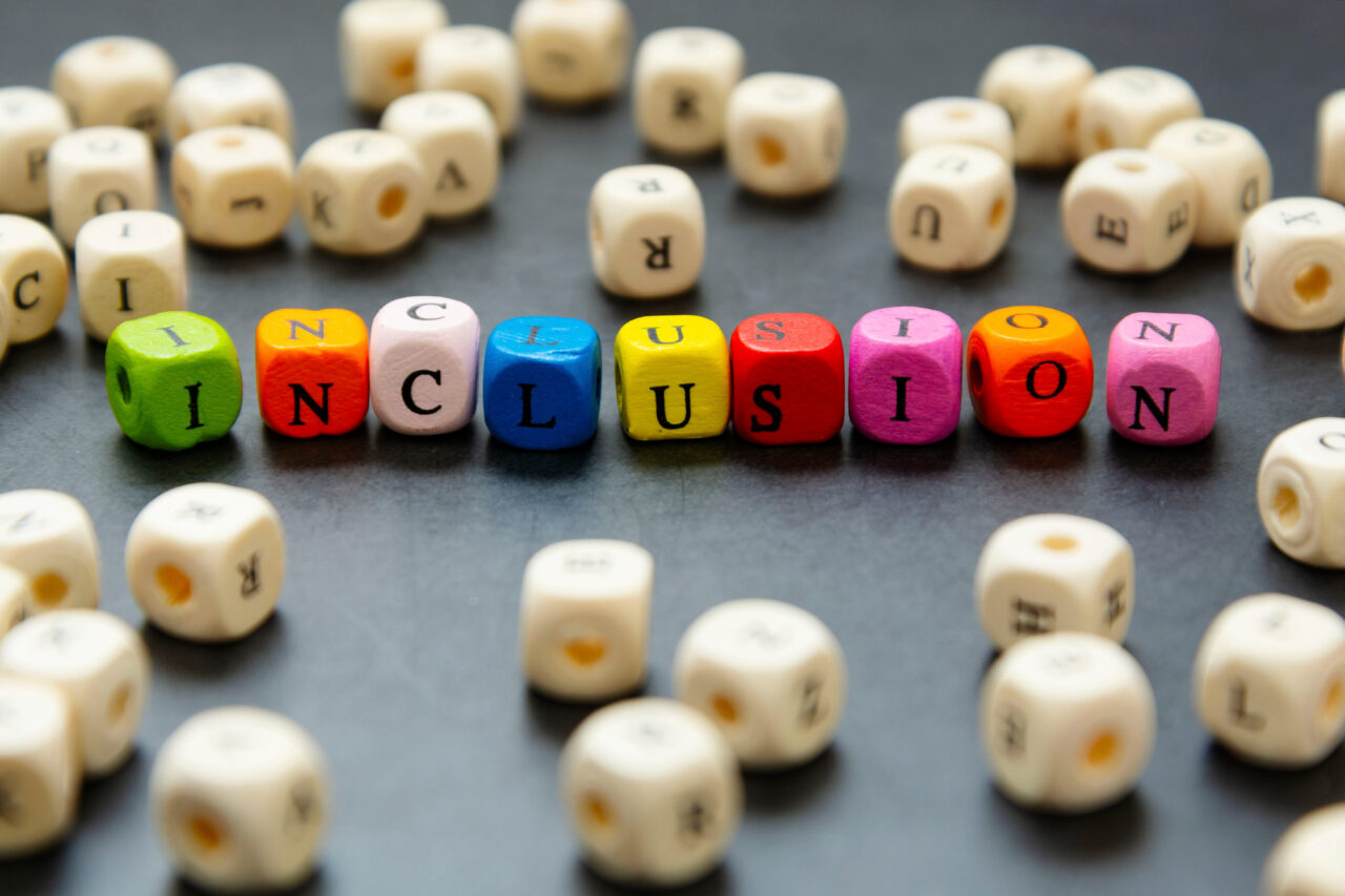 Wooden blocks set forming a word inclusion, which is an essential practice to focus on if you want to build your brand through accessibility and inclusion.