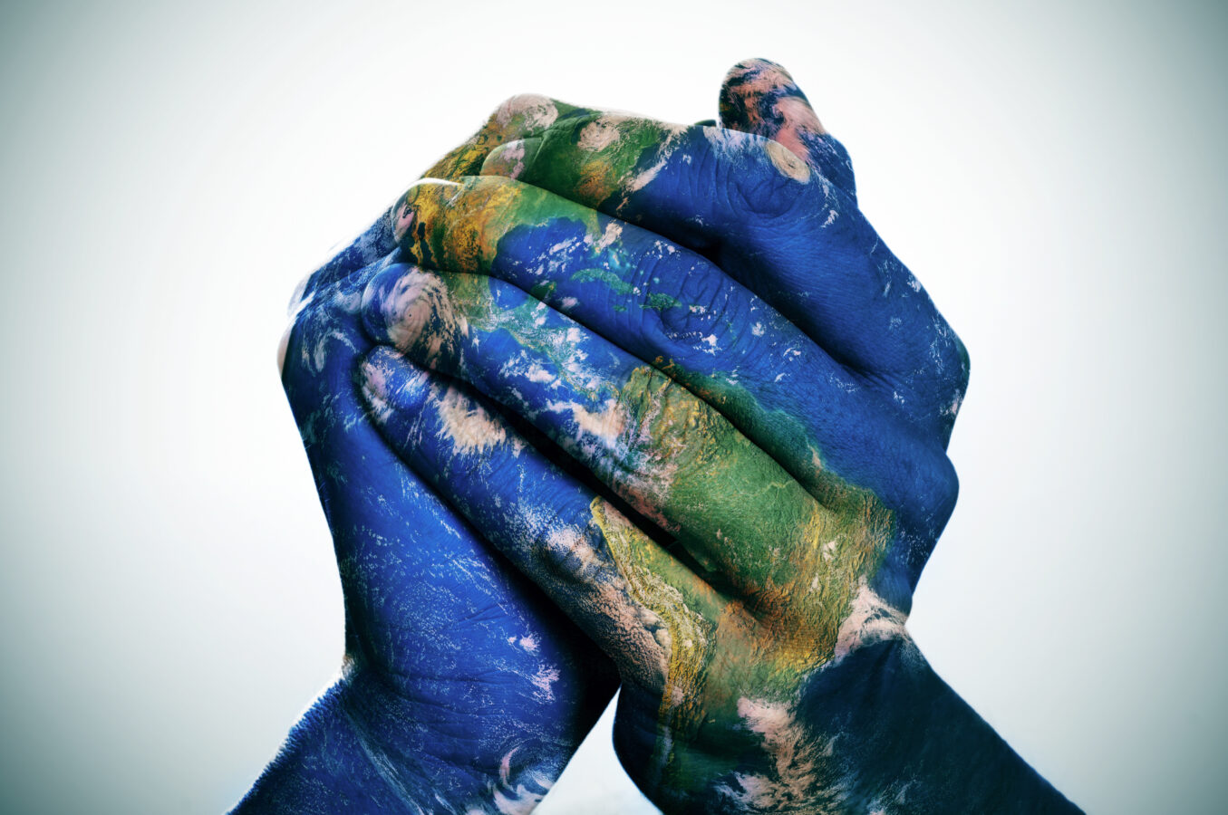 World map painted on hands to show cultural diversity.