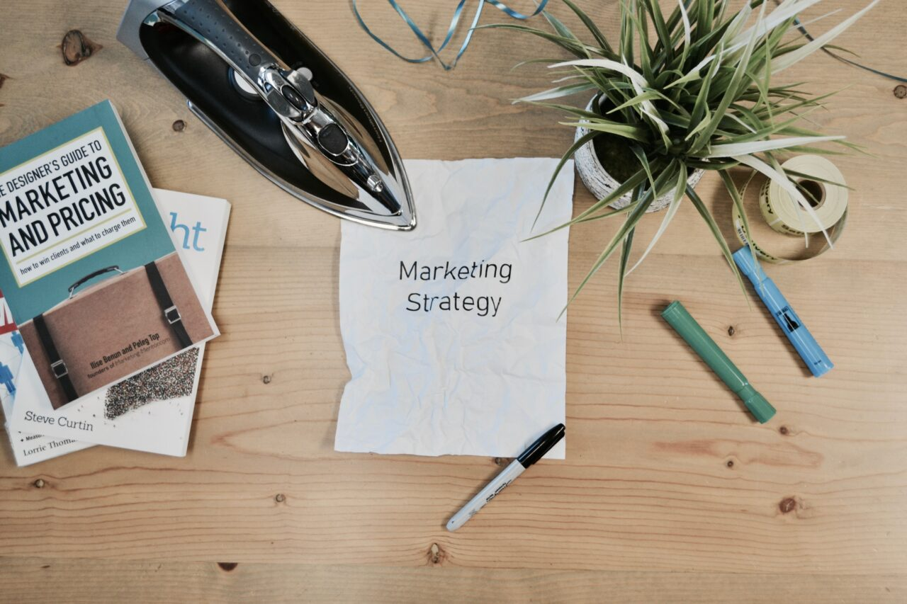 A desk of a digital marketer with books, pens, and a paper containing digital strategy.