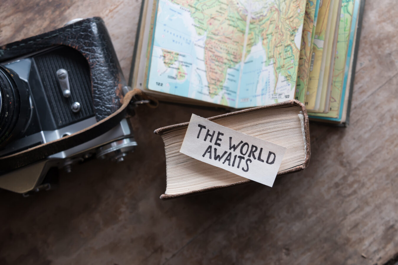 A paper on a world map says the world awaits the travel industry recovery.
