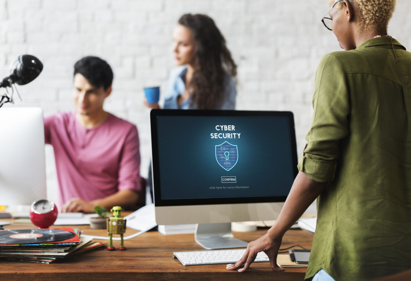 A team works in the office with protected laptops, showcasing the importance of having a fine balance between cybersecurity and remote working.