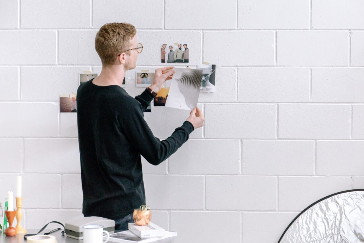 An employee adding photos to the wall to map and rethink customer experience.