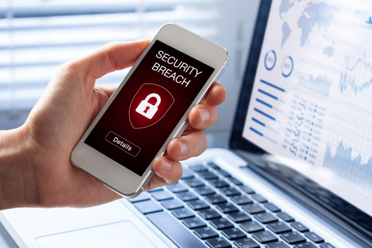 A person holds a phone with a security breach alert on the screen.