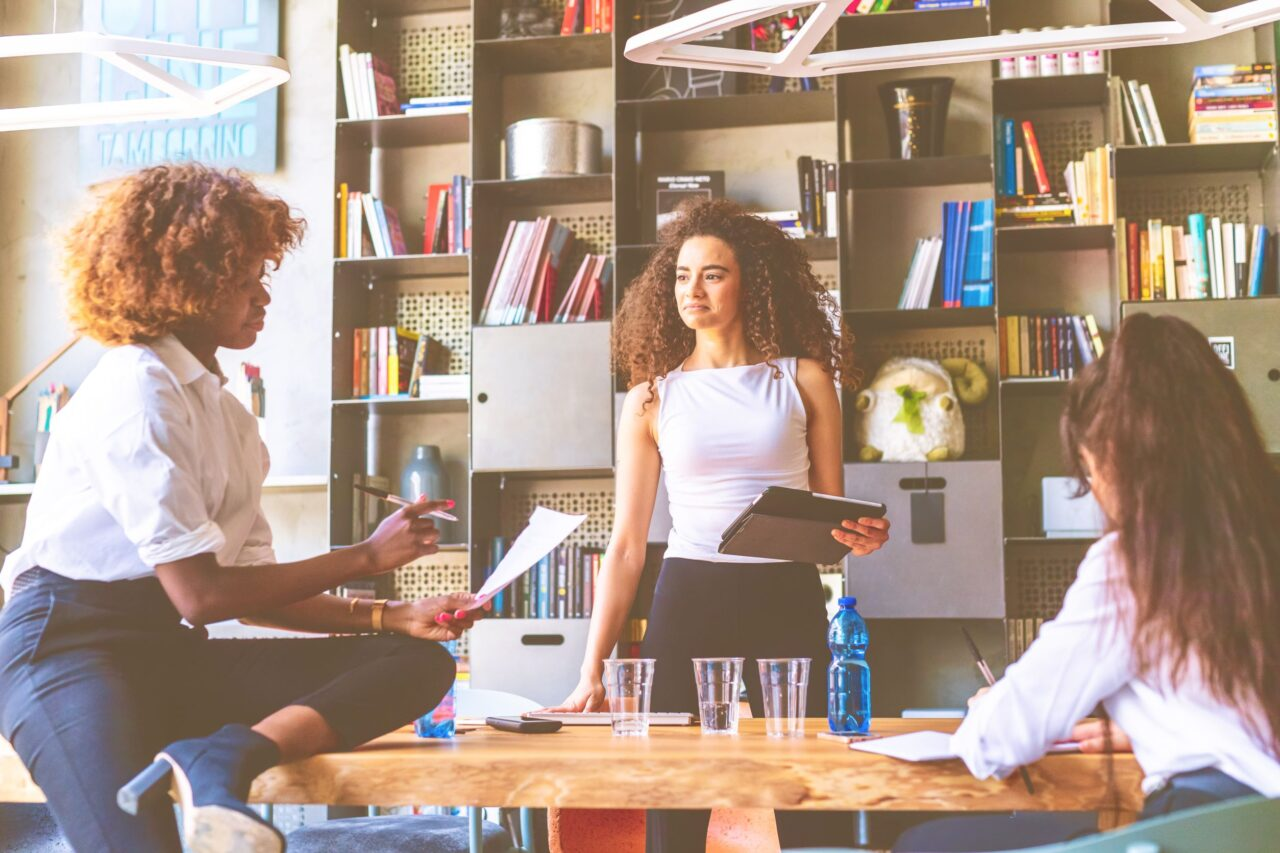 Two young women in the office talk about the steps to empower small businesses in post-COVID recovery.
