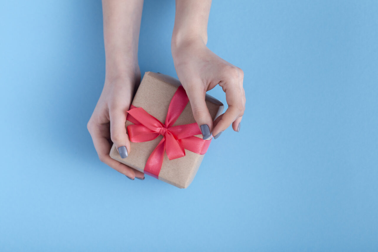 an image showing hands holding a gift as a symbol of customer loyalty.
