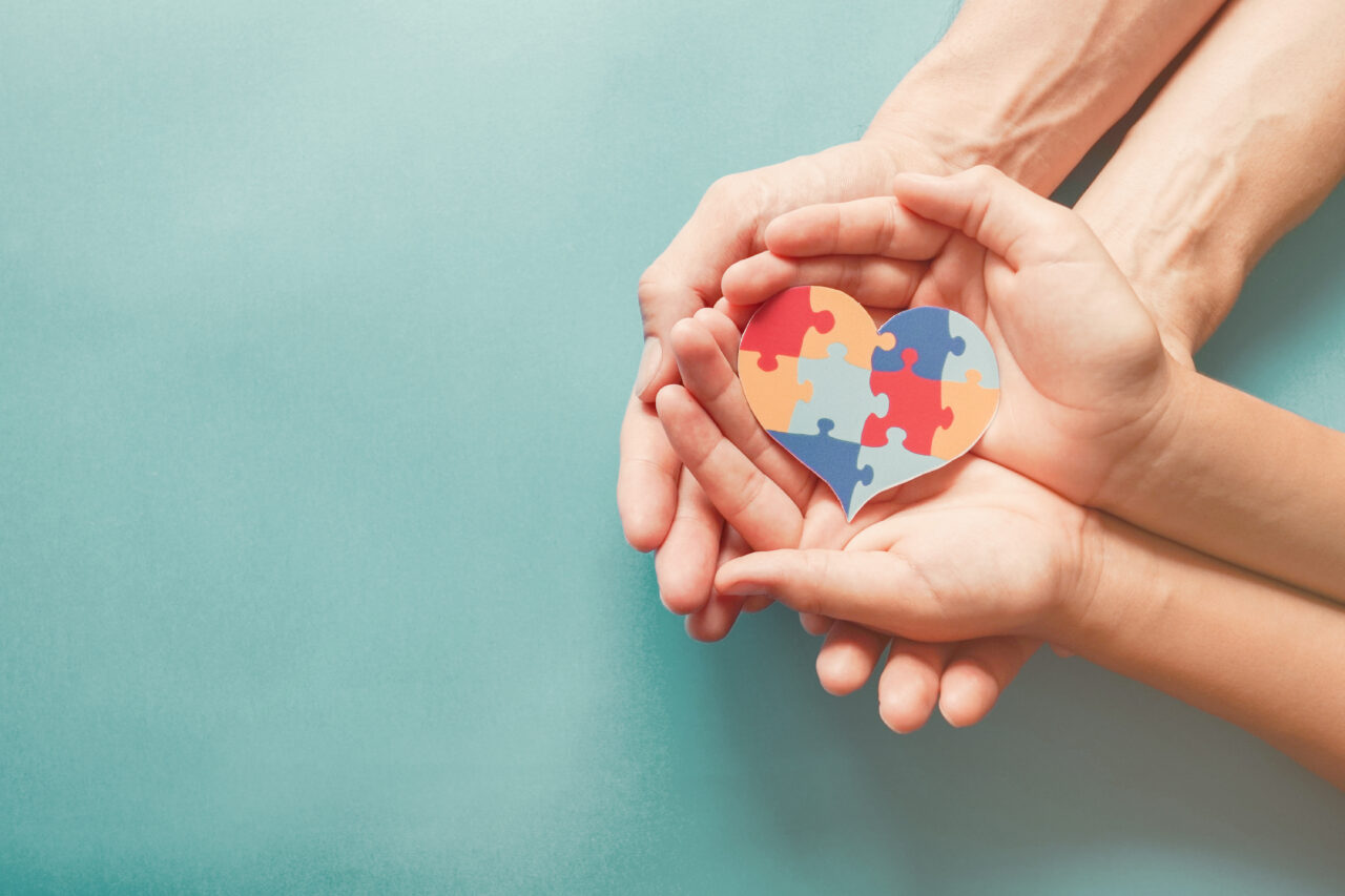 Two pairs of hands hold a jigsaw which stands for the importance of support and disability awareness.