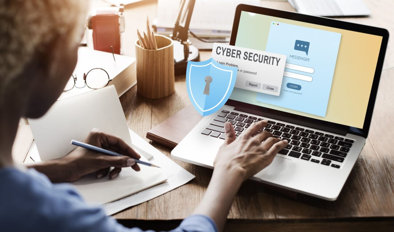 Cybersecurity and remote working showcased in a photo of a woman using a business laptop at home.