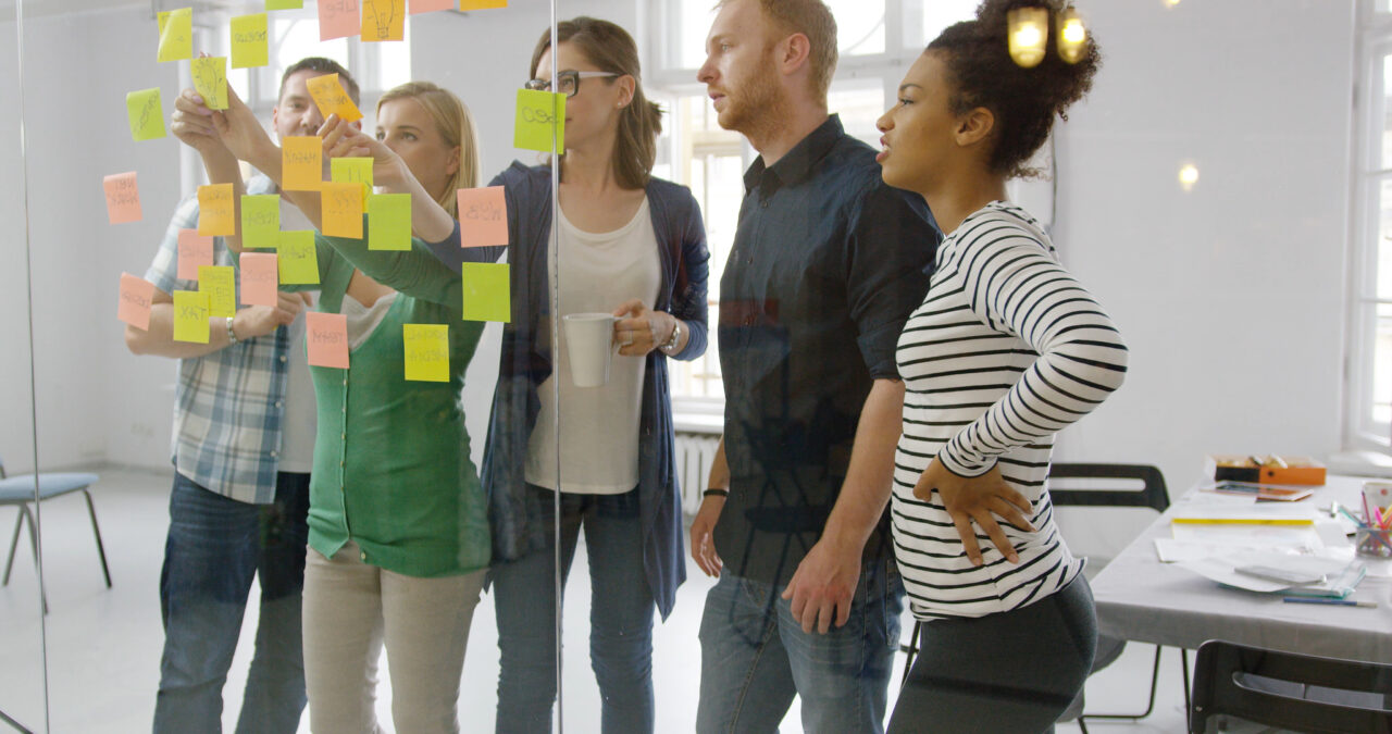 People look at the board covered in stickers with innovation ideas.