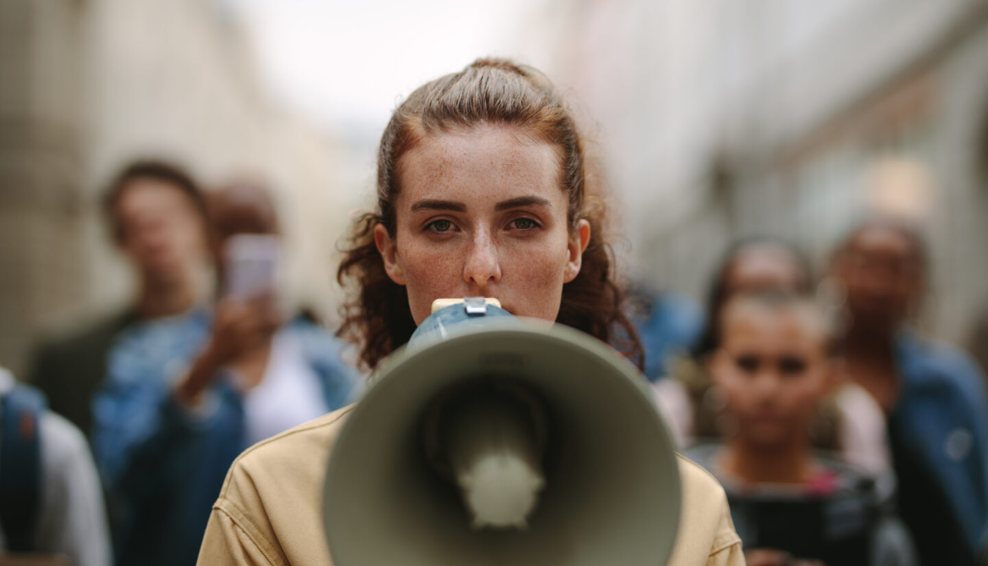 A woman speaks over a megaphone about a customer-focused revolution.
